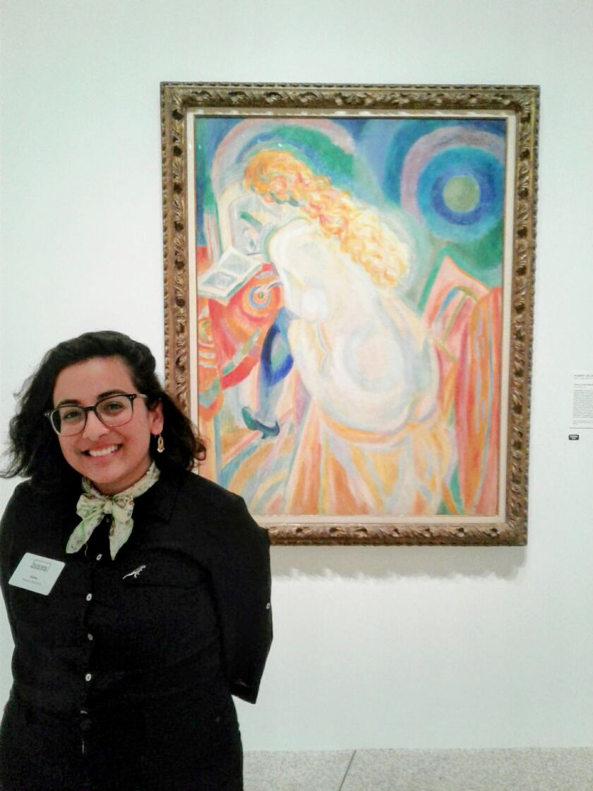 "Zelina Gaytan stands in front of ""Female Nude Reading,"" an oil painting at the San Diego Museum of Art."