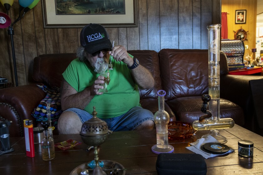 Ronnie Bell smokes cannabis oil in his living room
