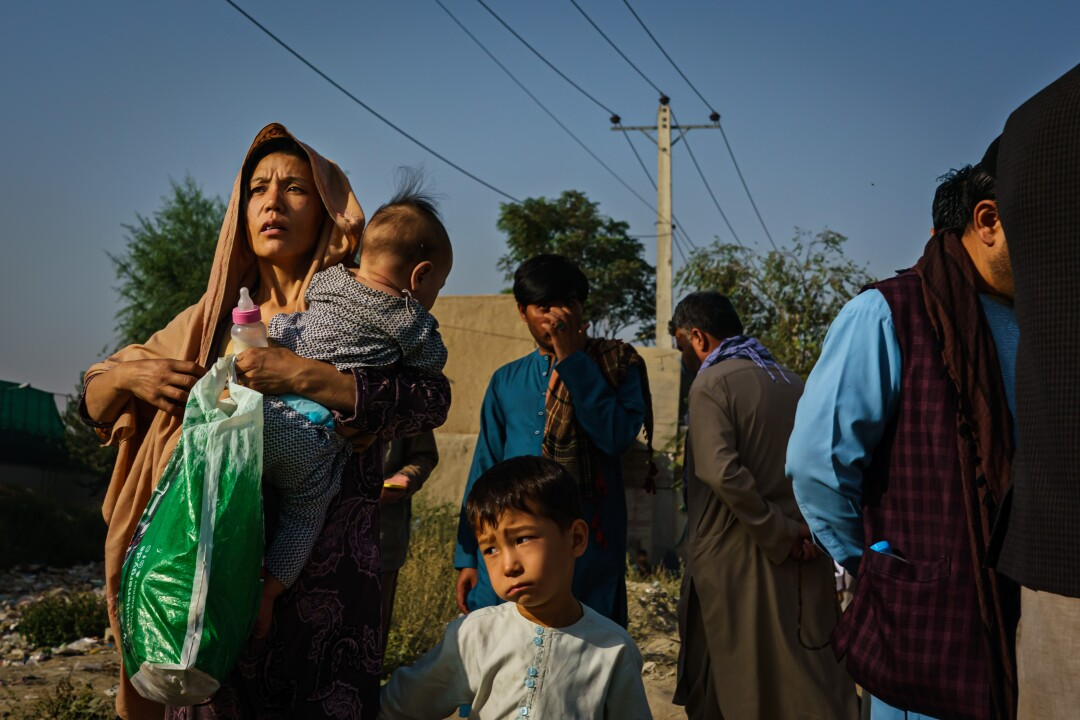 Afghans make their way the road to the military entrance of the airport for evacuations, in Kabul, Afghanistan.