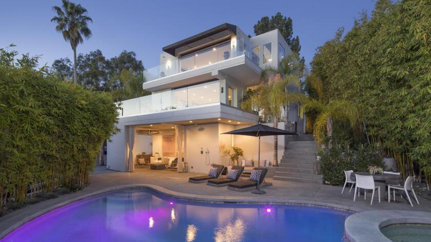 The renovated home in Hollywood Hills West features multiple terraces, a covered patio and a swimming pool.