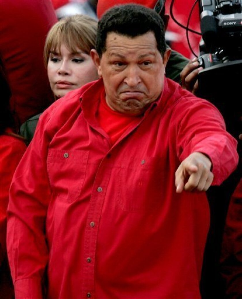Venezuela's President Hugo Chavez gestures during a rally in Caracas, Thursday, Feb. 12, 2009. Venezuelans will hold a referendum on Sunday, Feb. 15 to approve or not of a constitutional amendment which could allow Chavez and all other elected officials to run for re-election indefinitely. (AP Photo/Fernando Llano)