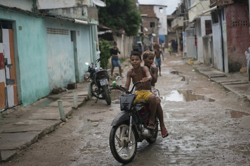 Boys ride a scooter at a slum in Recife, Pernambuco state, Brazil, Friday, Jan. 29, 2016. Brazilian officials still say they believe there's a sharp increase in cases of microcephaly and strongly suspect the Zika virus, which first appeared in the country last year, is to blame. The concern is strong enough that the U.S. Centers for Disease Control and Prevention this month warned pregnant women to reconsider visits to areas where Zika is present. (AP Photo/Felipe Dana)