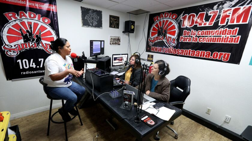 Carnaval Moralense USA organizer Dora Trejo, left, is interviewed at Radio Santa Ana by station coor