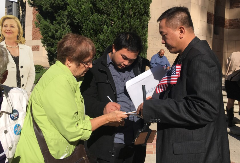 Thomas Macariola, center, fills out a voter registration form Oct. 26 after a naturalization ceremony in Sacramento.