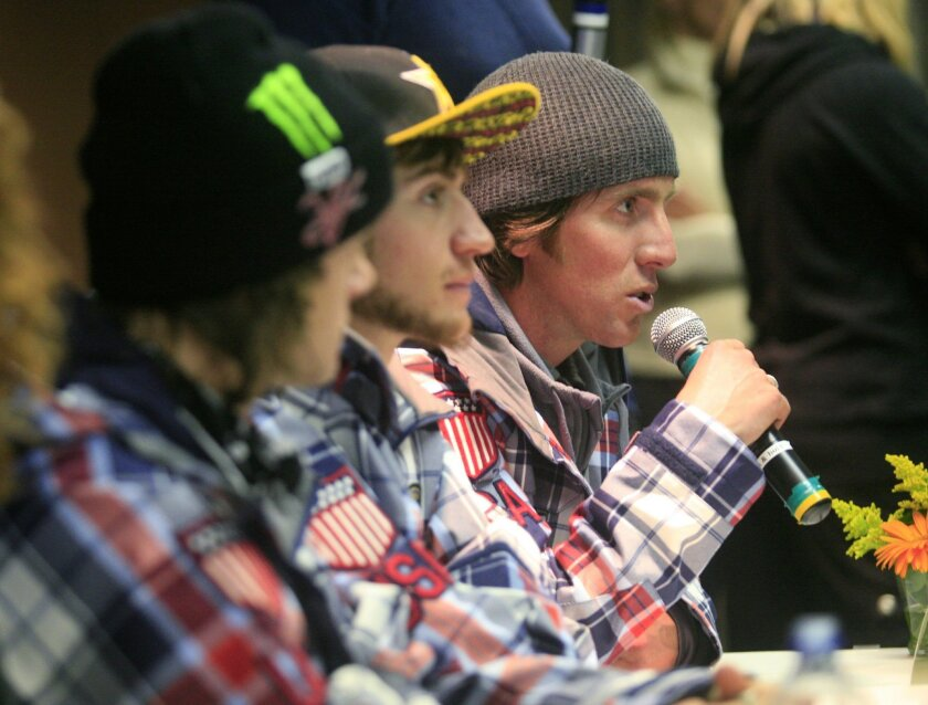 """FILE - In this Jan. 23, 2010, file photo, Mike Jankowski, right, coach for the U.S. Olympic snowboard team, answers a question at a news conference following the naming of the team, in Park City, Utah. From left are Louie Vito and Scott Lago. """"Sports is something that I've learned, first-hand, abou"""
