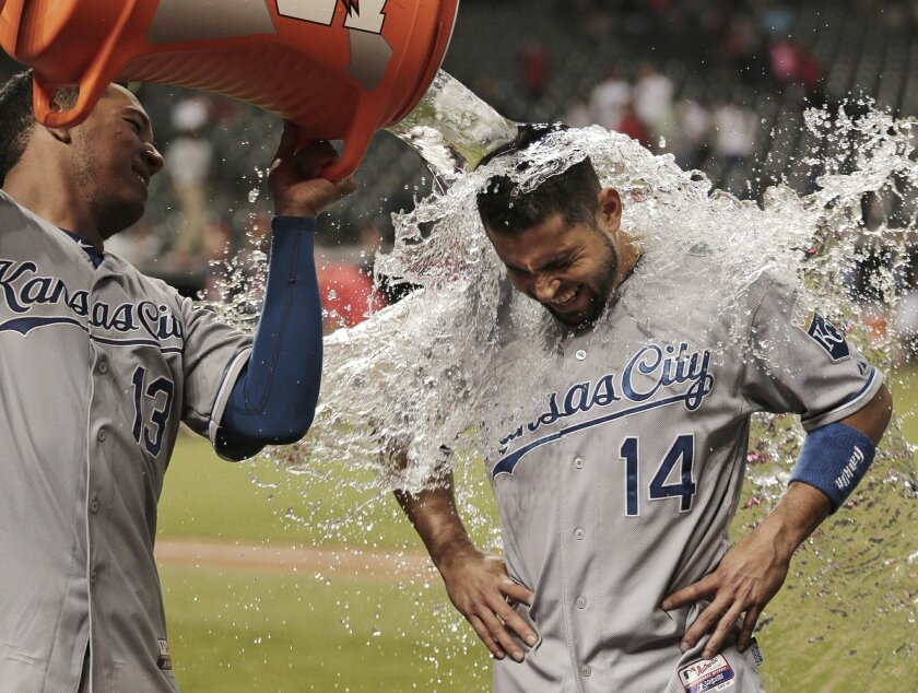 Kansas City Royals' Salvador Perez pours water onto Omar Infante after the Royals defeated the Cleveland Indians 8-4 in a baseball game, Thursday, Sept. 17, 2015, in Cleveland. (AP Photo/Tony Dejak)
