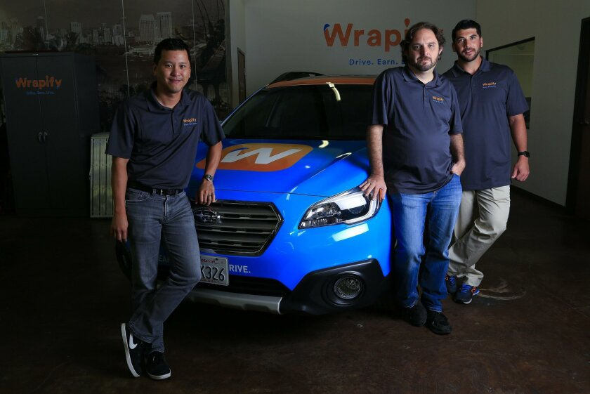 SAN DIEGO, CA-SEPTEMBER 21, 2015: | At the Wrapify office in Sorrento Valley co-founders (left-to-right) Phil Chen CTO, Tim Flack, VP of Engineering and James Heller CEO show off one of their wrapped cars.