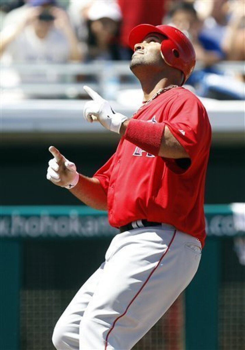 Los Angeles Angels' Albert Pujols points skyward as he crosses home plate after hitting a two-run home run off Chicago Cubs pitcher Paul Maholm in the first inning of a spring training baseball game Saturday, March 31, 2012, in Mesa, Ariz. (AP Photo/Paul Connors)