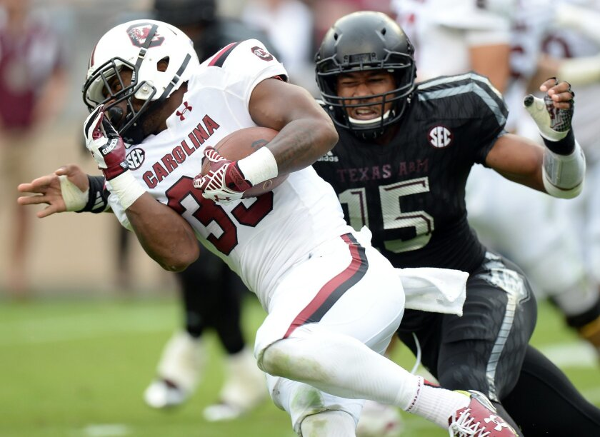 Texas A&M's Myles Garrett (15) tackles South Carolina's David Williams (33) after a short gain during the first quarter of an NCAA college football game on Saturday, Oct. 31, 2015  in College Station, Texas.   (Sam Craft/College Station Eagle via AP) MANDATORY CREDIT