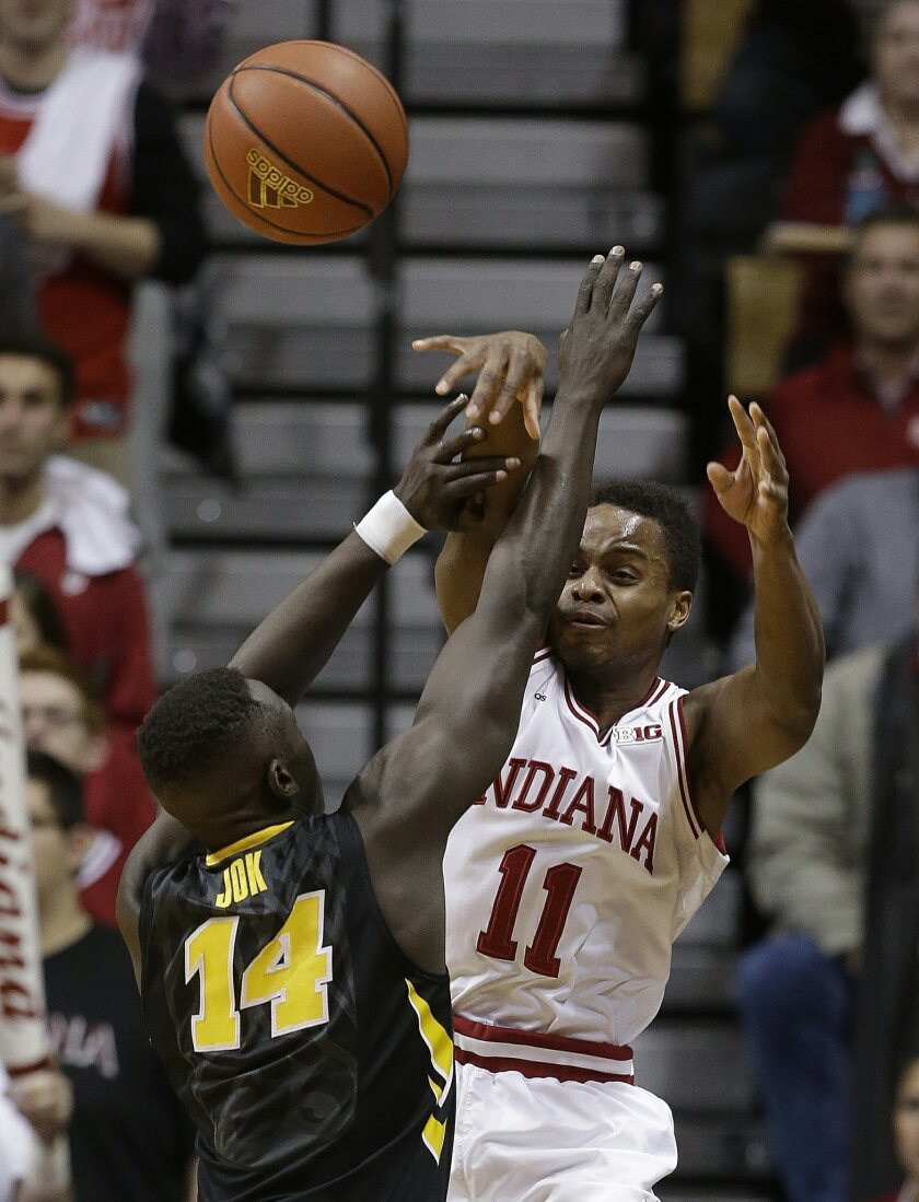 Indiana's Yogi Ferrell (11) passes over Iowa's Peter Jok (14) during the first half of an NCAA college basketball game Thursday, Feb. 11, 2016, in Bloomington, Ind. (AP Photo/Darron Cummings)