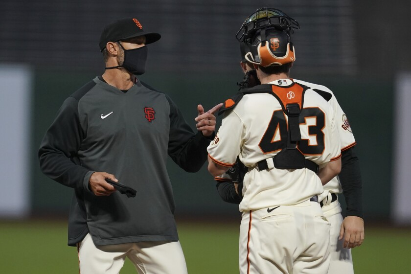 San Francisco Giants manager Gabe Kapler, left, talks with catcher Tyler Heineman (43) and pitcher Caleb Baragar during the fifth inning of a baseball game against the San Diego Padres in San Francisco, Thursday, July 30, 2020. (AP Photo/Jeff Chiu)