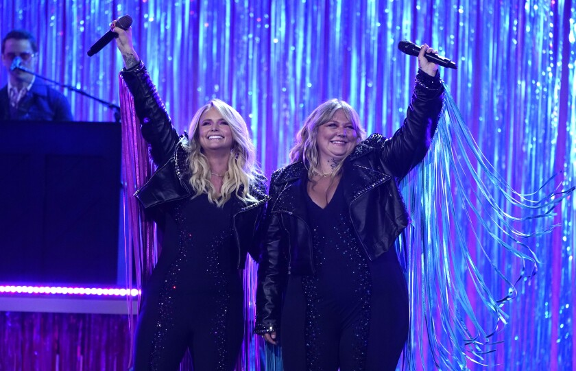 Smiling together on stage, Miranda Lambert, left, and Elle King hold their microphones high