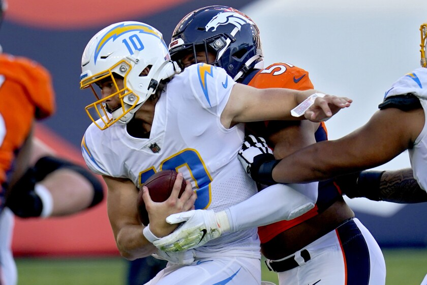 Los Angeles Chargers quarterback Justin Herbert (10) is sacked by Denver Broncos defensive end DeMarcus Walker (57) during the first half of an NFL football game, Sunday, Nov. 1, 2020, in Denver. (AP Photo/Jack Dempsey)