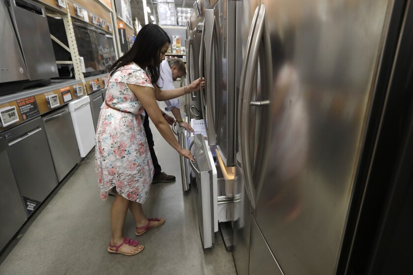 FILE - In this Sept. 23, 2019, file photo shoppers examine refrigerators at a Home Depot store location, in Boston. On Tuesday, Oct. 29, the Conference Board reports on U.S. consumer confidence for October. (AP Photo/Steven Senne, File)