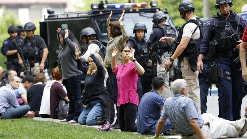 La policía revisa a algunos estudiantes después de la balacera en UCLA.