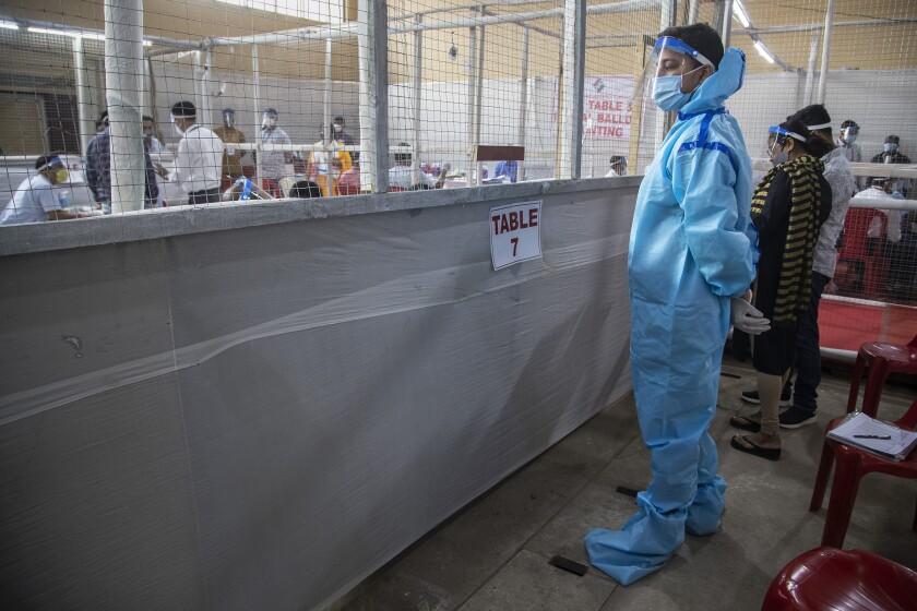 Un agente de conteo, de pie con un traje de protección, supervisa el conteo de votos en las elecciones