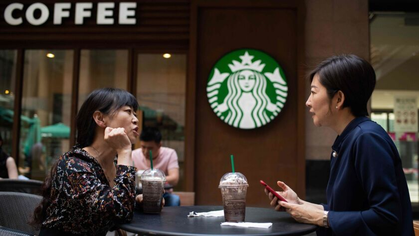 Women talk at a Starbucks coffee shop in Beijing. Starbucks wants to more than triple its revenue from China over the next five years.