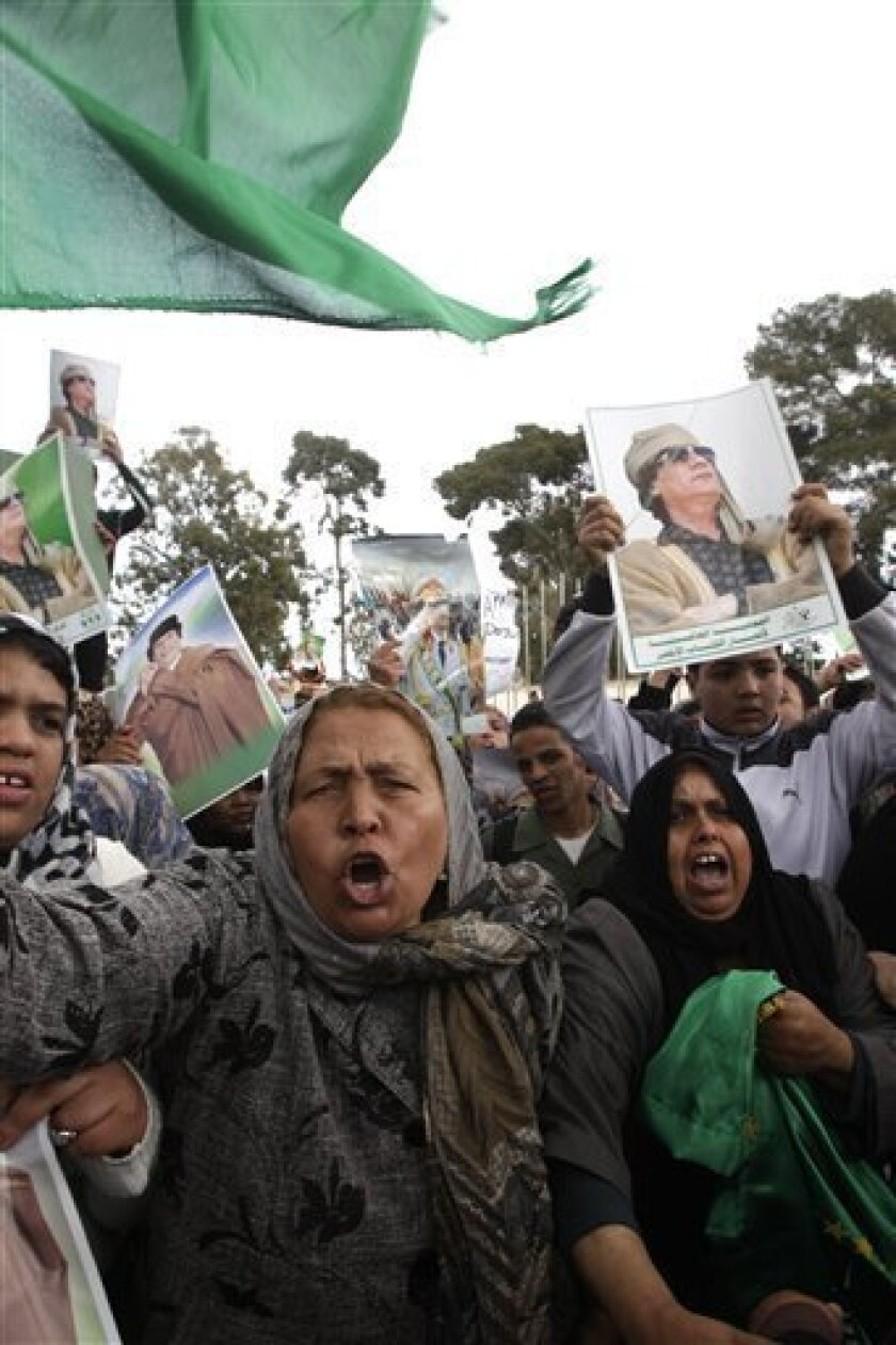 Libyan supporters of Moammar Gadhafi take part in a demonstration outside a hotel where most of the foreign media representative are staying, in Tripoli, Libya, Thursday, March 31, 2011. The defection of Libya's foreign minister, a member of Moammar Gadhafi's inner circle, is the latest sign that t