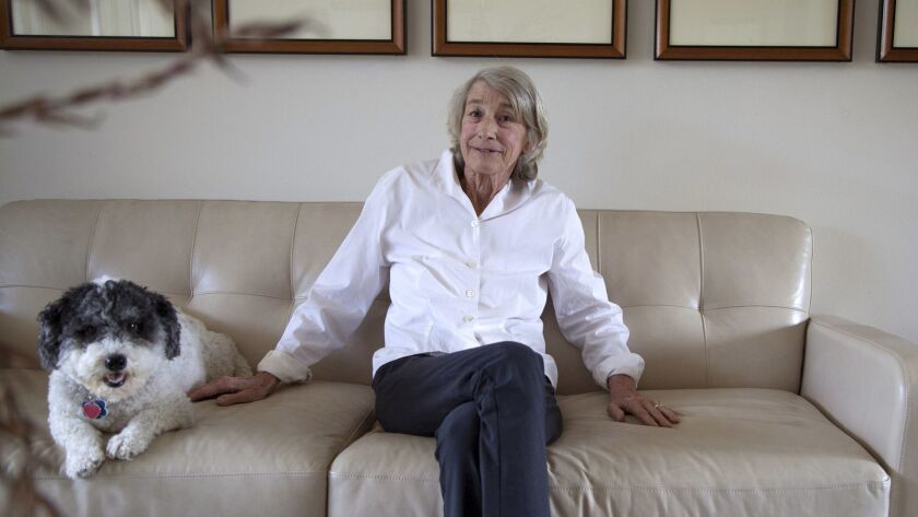 In a file photo from 2013, poet Mary Oliver sits with her dog, Ricky, at her home in Hobe Sound, Fla. Oliver died on Jan. 17, 2019, She was 83.