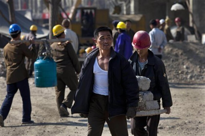 In this Tuesday Oct. 11, 2011 photo, North Korean construction workers carry building materials in the Mansudae area of Pyongyang, North Korea. Throughout the capital, and in cities and towns across the country, construction workers are trying to finish building renovations and major projects as th