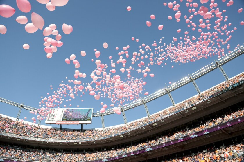 "FILE - In this Oct. 13, 2013, file photo, Pink balloons are released inside Sports Authority Field at Mile High Stadium to commemorate Breast Cancer Awareness month during halftime of an NFL football game between the Denver Broncos and Jacksonville Jaguars in Denver. The NFL's fourth annual ""Breast Cancer Awareness Month"" kicks off Thursday night, Oct. 2, 2014, with the Viking at the Packers and runs through October. (AP Photo/Joe Mahoney, File)"