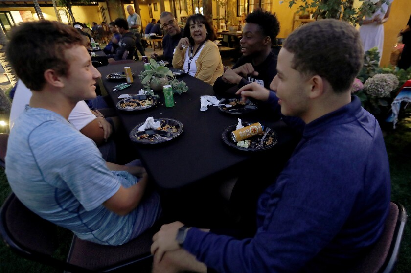 embers of the Chicago Hope Academy and Bishop Diego football teams talk over dinner on Sept. 19, 2019.