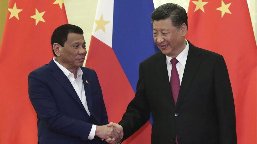 FILE - In this April 25, 2019, file photo, Philippine President Rodrigo Duterte, left, shakes hands