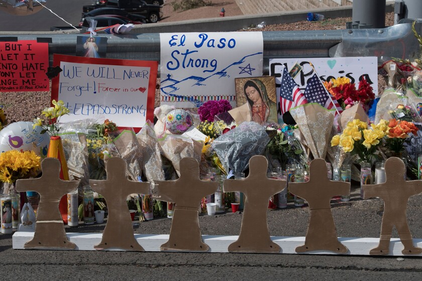 Signs, flowers, flowers, U.S. flags and an image of the Virgin Mary at a makeshift memorial for El Paso shooting victims.