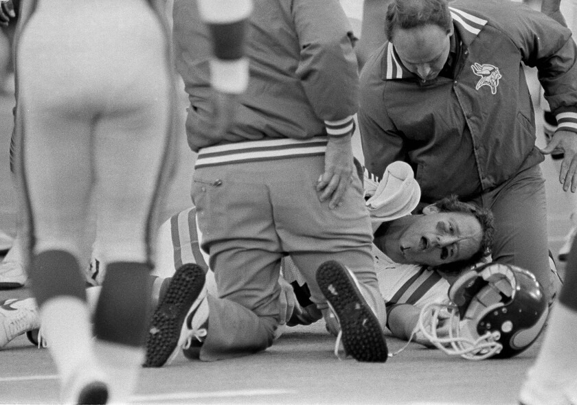 Minnesota Vikings auarterback Archie Manning is attended to by a team trainer after being sacked during a game against the Chicago Bears in Chicago on Oct. 28, 1984. Manning left the game after being sacked 11 times-- a new Bears record.