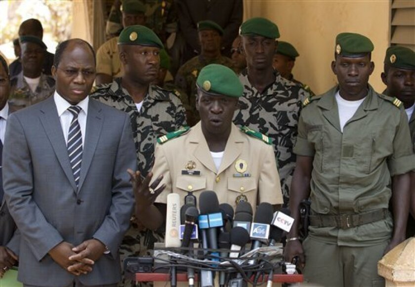 Coup leader Capt. Amadou Haya Sanogo, center, is accompanied by Burkina Faso Foreign Affairs Minister Djibril Bassole, left, as he addresses the press at junta headquarters in Kati, outside Bamako, Mali Sunday, April 1, 2012. The leader of Mali's recent coup says he is reinstating the nation's previous constitution amid international pressure to restore constitutional order. Sanogo said a national convention would be held to organize elections, but he failed to announce a timeline for the elections.(AP Photo/Rebecca Blackwell)