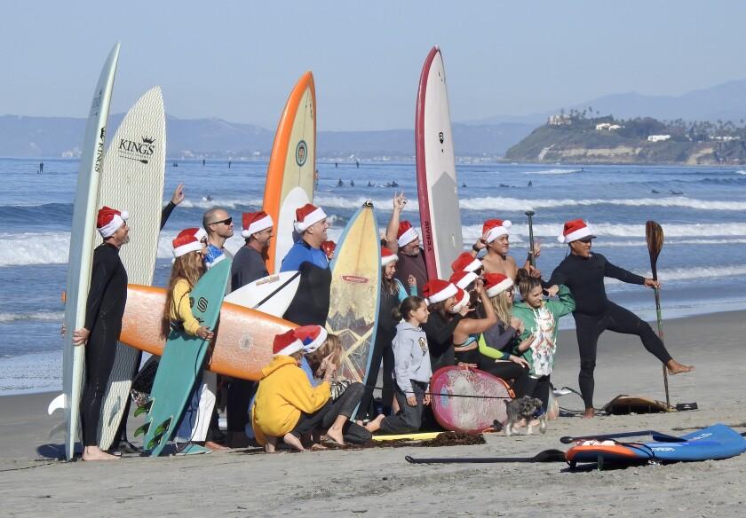 Tis the season to surf in Santa caps at Solana Beach