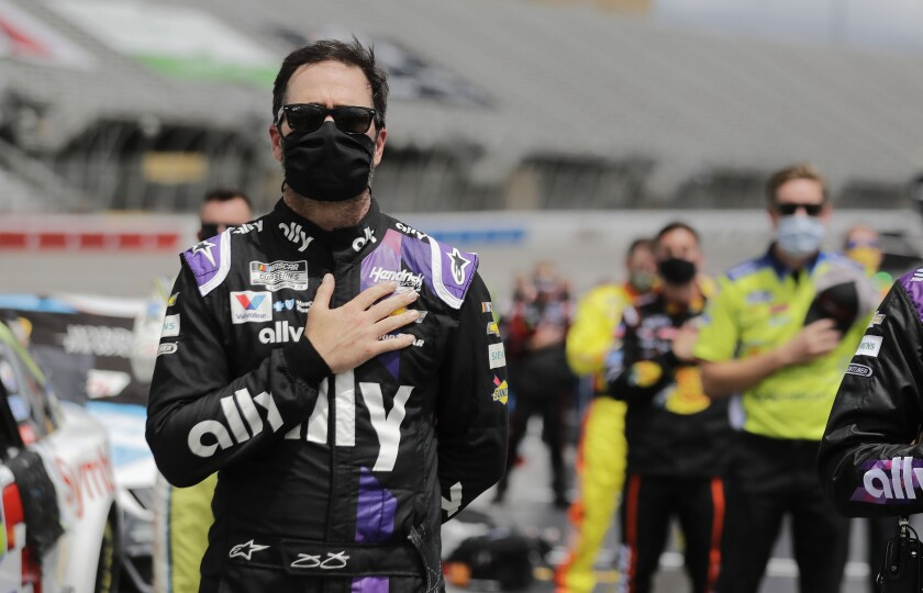 Jimmie Johnson stands with crew members during the national anthem Sunday at Atlanta Motor Speedway.