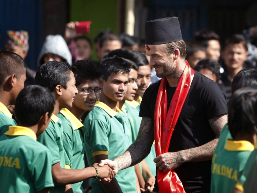 Former soccer player David Beckham shakes hands with Nepalese student in Bhaktapur, Nepal, Friday, Nov. 6, 2015. Beckham is in Nepal filming a documentary for UNICEF. He played soccer with Nepalese children and visited a school in Bhaktapur that was damaged in April's devastating earthquake. (AP Ph