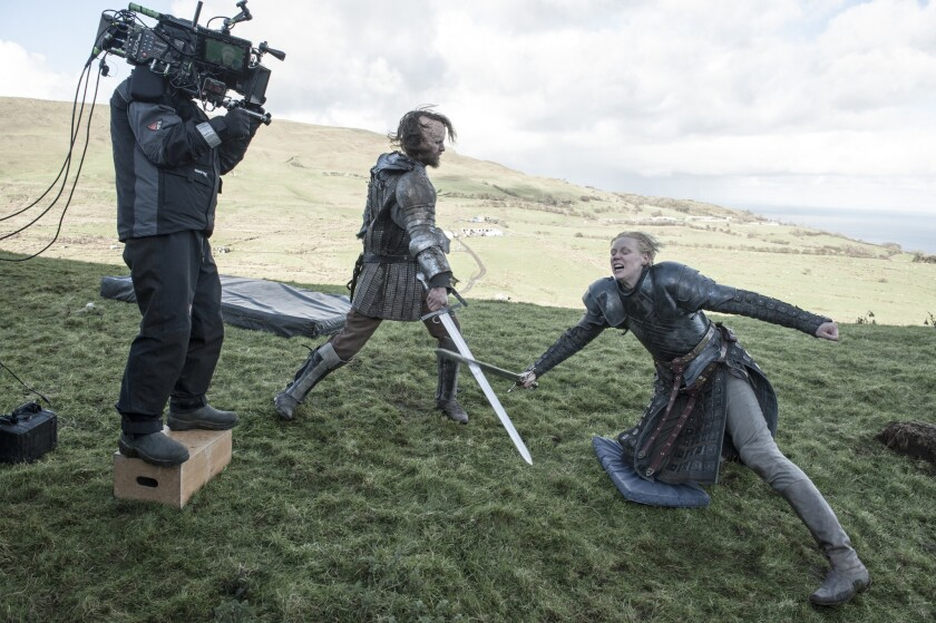 """On location in the countryside of Northern Ireland, a """"Game of Thrones"""" cameraman photographs a sword-fight scene between Rory McCann, center, and Gwendoline Christie."""