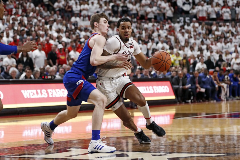 FILE - Texas Tech's Kyler Edwards (0) drives against Kansas' Christian Braun (2) during the second half of an NCAA college basketball game n Lubbock, Texas, in this Saturday, March 7, 2020, file photo. Texas Tech is technically still the reigning national runner-up since there was no NCAA Tournament played last season. The Red Raiders were on the floor warming up for their Big 12 tournament opener last March when the season suddenly stopped because of the novel coronavirus pandemic. (AP Photo/Brad Tollefson, File)