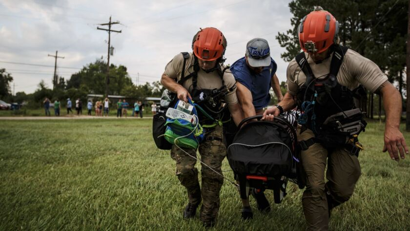 Members of the California Air National Guard 129th Rescue Wing help a man carry his infant with a se
