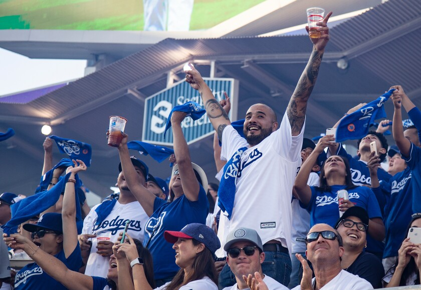 Dodger fans cheer as the Dodgers starting line-up is announced before a game at Dodger Stadium.
