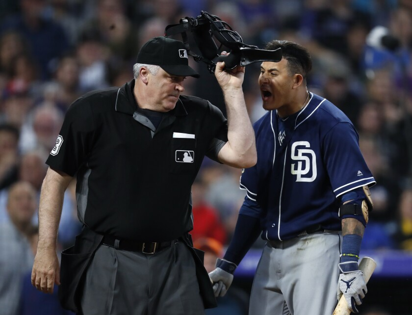 San Diego Padres' Manny Machado, right, yells at home plate umpire Bill Welke, who had called Machado out on strikes during the fifth inning of the team's baseball game against the Colorado Rockies on Saturday, June 15, 2019, in Denver.