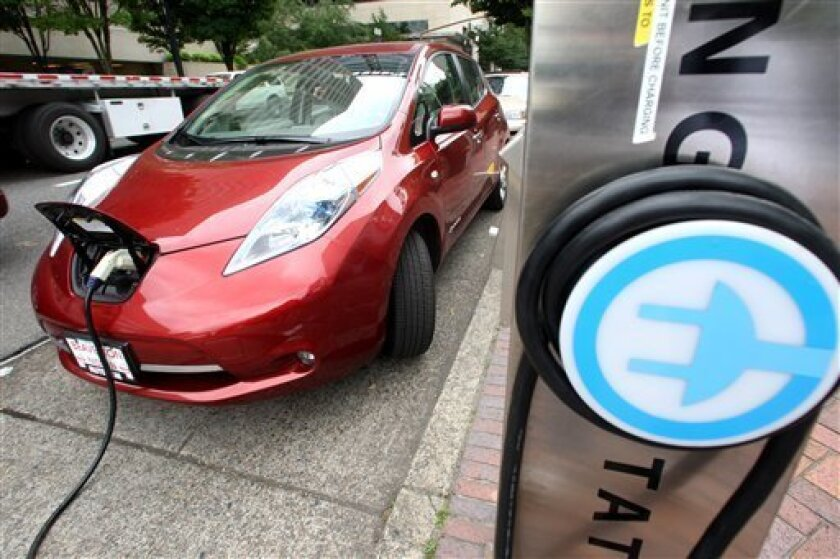 A Nissan Leaf charges at a electric vehicle charging station Thursday, Aug. 18, 2011, in Portland, Ore. More electric car fast-charging stations are coming to Oregon. The Oregon Department of Transportation announced Thursday that 22 of them will be built next year in the northwestern corner of the