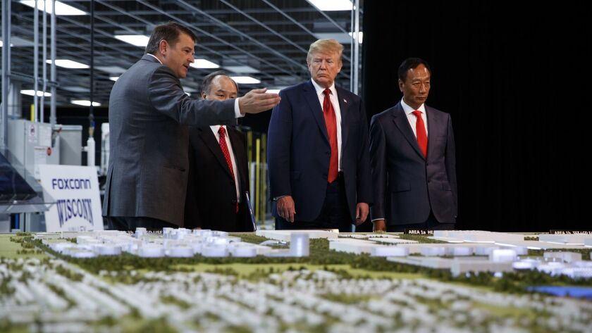 President Trump, second from right, looks at Foxconn's plans for a factory in Mt. Pleasant, Wis., with Foxconn Chairman Terry Gou, right, in 2018. Foxconn, which won a $4.5-billion incentive package from Wisconsin, indicated it is reconsidering developing LCD displays there.