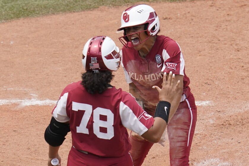 Oklahoma's Rylie Boone, right, celebrates with teammate Jocelyn Alo (78) after scoring on a hit by Tiara Jennings in the seventh inning of an NCAA Women's College World Series softball game Sunday, June 6, 2021, in Oklahoma City. (AP Photo/Sue Ogrocki)