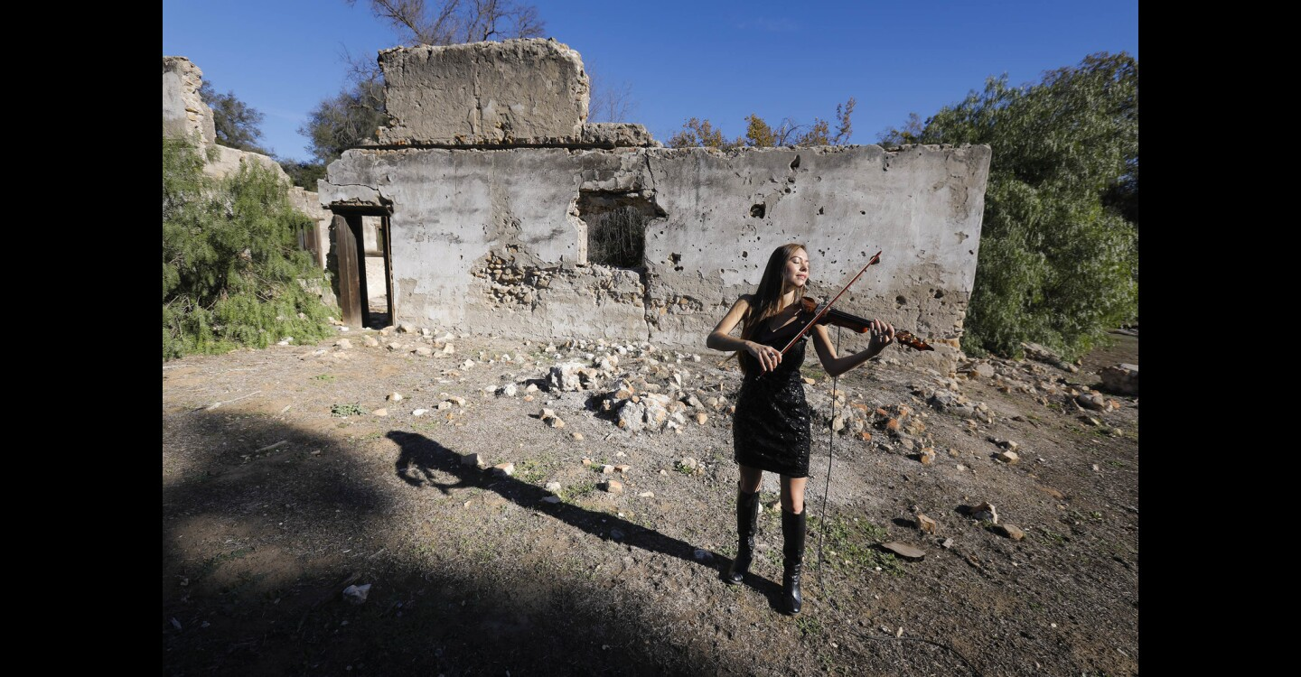 Amy Serrano Burcombe plays the electric violin with the backdrop of the Maxcy Winery ruins, circa 1852, at Rancho Guejito, one of the stops on the Rancho Guejito Vineyard wine tasting adventure when they begin being offered to the public in the near future.