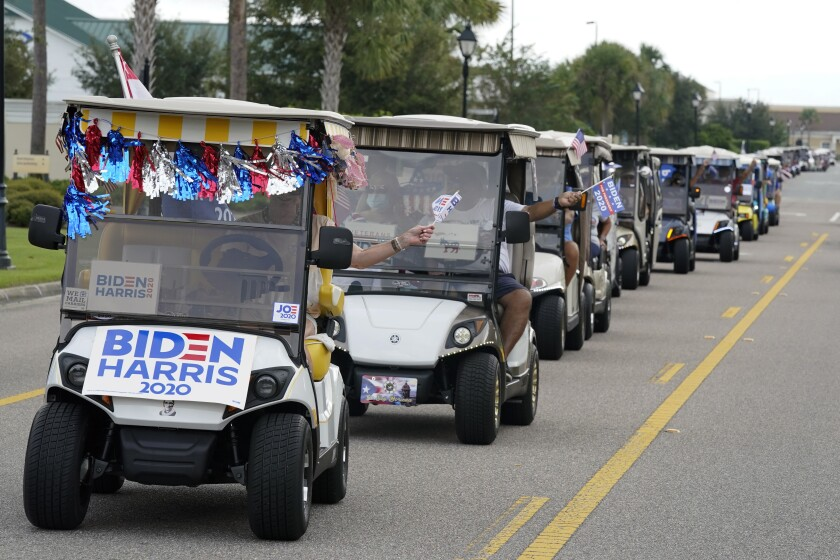 A parade of Biden supporters ride golf carts to an elections office to cast their ballots in The Villages.