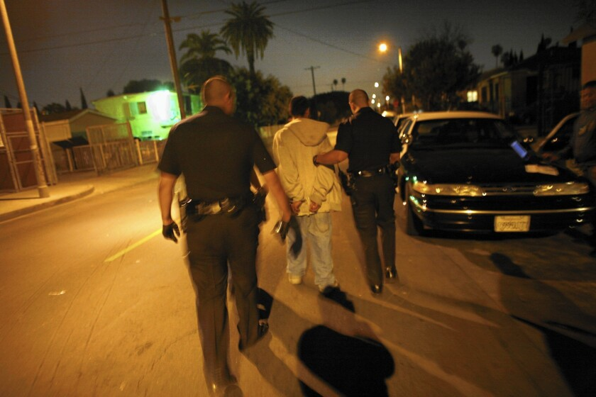 LAPD officers arrest a suspected gang member in 2009, during the period when violent crimes were underreported by 7%.