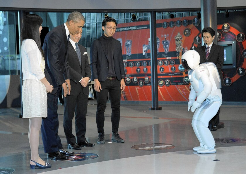 President Obama interacts with a robot known as ASIMO during a youth science event at the National Museum of Emerging Science and Innovation in Tokyo.