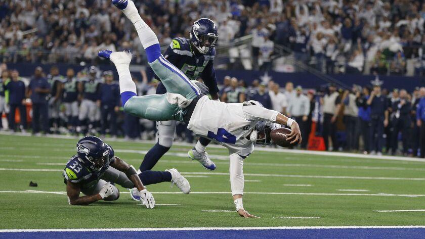 Dallas Cowboys quarterback Dak Prescott (4) flies for the goal line and makes a first down against S
