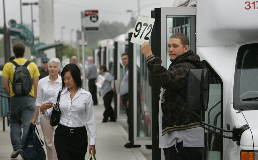 David Solano (right) held a sign with a route number for commuters arriving at the Coaster station in Sorrento Valley. His shuttle is one of two that go to the Qualcomm offices. (Howard Lipin / Union-Tribune)