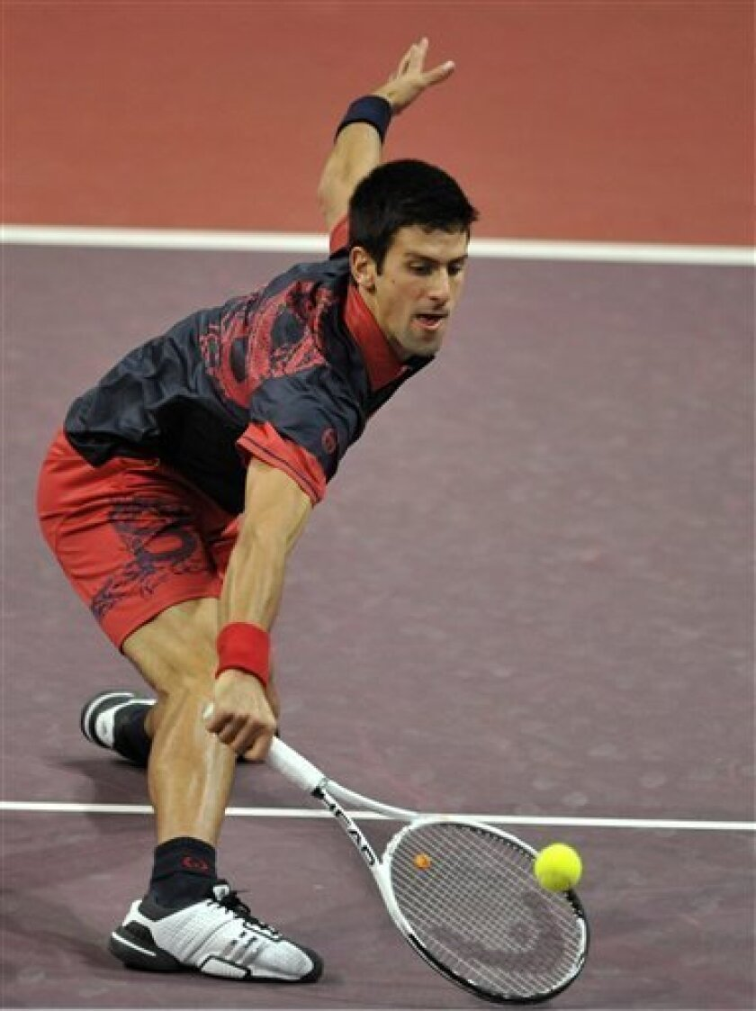 Serbia's Novak Djokovic returns a ball to Serbia's Viktor Troicki during their semifinal match at the Davidoff Swiss Indoors tennis tournament at the St. Jakobshalle in Basel, Switzerland, Saturday, Nov. 6, 2010. (AP Photo/Keystone, Georgios Kefalas)