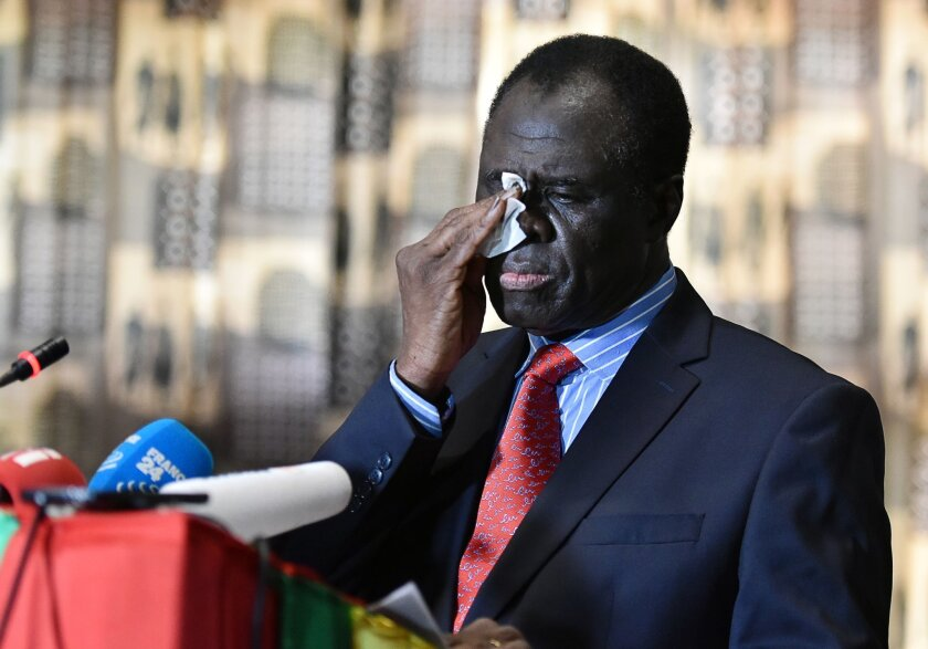 Burkina Faso President Michel Kafando wipes his face as he delivers a statement to the media on Sept. 23