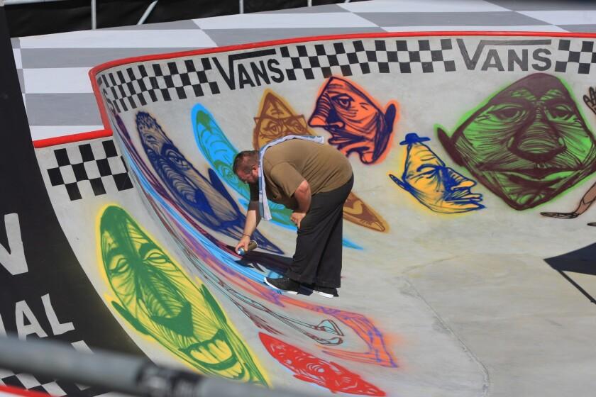 Rich Jacobs paints a mural on the Van Doren Invitational Skate Bowl competition site.